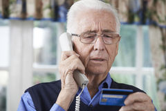 Senior Man Giving Credit Card Details On The Phone Royalty Free Stock Photos