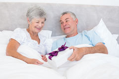 Senior man giving gift box to wife in bed Stock Images