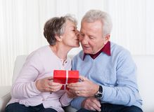 Senior Man Giving Gift To Senior Woman Royalty Free Stock Photo
