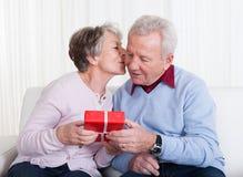 Senior Man Giving Gift To Senior Woman Royalty Free Stock Photo
