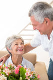 Senior man giving his partner a bouquet of flowers Royalty Free Stock Images