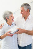 Senior man giving his surprised partner a gift Royalty Free Stock Photos