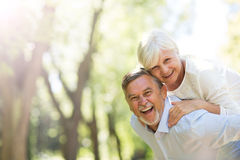 Senior man giving his wife a piggyback outdoors. Loving senior couple standing outdoors Royalty Free Stock Photo
