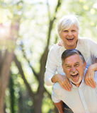 Senior man giving his wife a piggyback outdoors. Loving senior couple standing outdoors Royalty Free Stock Images