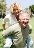 Senior man giving piggy ride to her wife Stock Image