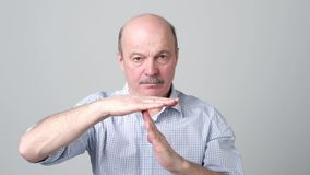 Senior man giving showing time out hands gesture. Isolated on gray wall background stock video footage