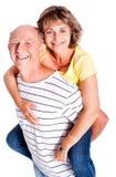 Senior man giving woman piggyback ride Stock Image