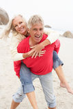 Senior Man Giving Woman Piggyback On Winter Beach Stock Photos