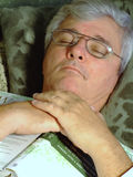 Senior Man with Glases taking a Nap. Mature man, wearing glasses, sleeping with a book Royalty Free Stock Photography