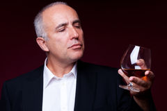 Senior man with glass of brandy Stock Photography