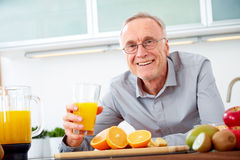 Senior man with a glass of orange juice Stock Photo
