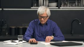 Senior man in glasses considers expenses Royalty Free Stock Images