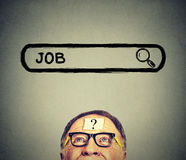 Senior man in glasses looking up searching for a job. Royalty Free Stock Images