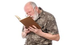 Senior man with glasses reading a book. Handsome bald and bearded bad seeing senior man with glasses reading a book, isolated on white background Royalty Free Stock Photography