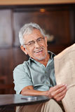 Senior man with glasses reading newspaper Royalty Free Stock Images