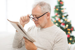 Senior man in glasses reading newspaper at home Stock Photography