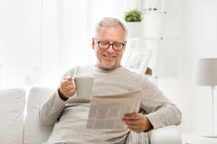 Senior man in glasses reading newspaper at home. Leisure, information, people and mass media concept - senior man in glasses reading newspaper at home Royalty Free Stock Photos