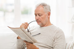 Senior man in glasses reading newspaper at home Royalty Free Stock Image