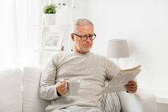 Senior man in glasses reading newspaper at home Stock Photo