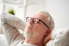 Senior man in glasses relaxing on sofa. Old age, comfort and people concept - senior man in glasses relaxing on sofa at home Stock Photography