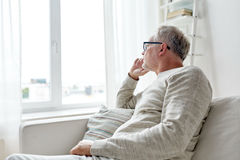 Senior man in glasses thinking at home Stock Photography