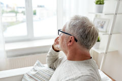 Senior man in glasses thinking at home Royalty Free Stock Photography