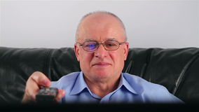 Senior man with glasses watching TV Royalty Free Stock Photo