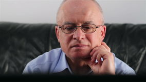 Senior man with glasses watching TV Royalty Free Stock Photos