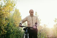 Senior man go for a walk with bike in countryside. Senior caucasian man go for a walk with bike in countryside. Green trees on background. He is happy and active royalty free stock image