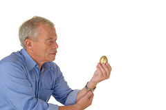 Senior man with golden egg Stock Photos