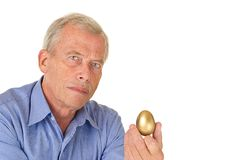 Senior man with golden egg Stock Images