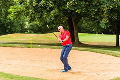 Senior man at golf having stroke in sand bunker Stock Images