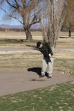 Senior Man Golfing. Out of sand bunker in Arizona in the winter time Stock Photography