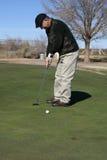 Senior Man Golfing. Senior Man putting on green in Arizona in the winter time Royalty Free Stock Image
