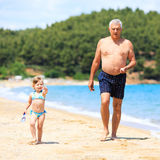 Senior man with granddaughter on the beach Royalty Free Stock Images
