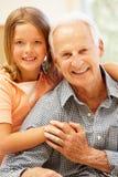 Senior man and granddaughter at home Royalty Free Stock Photo