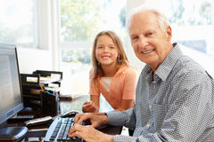 Senior man and granddaughter using computer Royalty Free Stock Photography