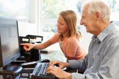 Senior man and granddaughter using computer Royalty Free Stock Images