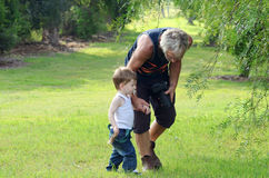 Senior man grandfather walking talking in park with grandson boy Stock Photos