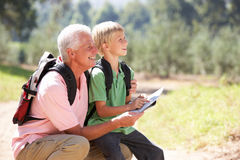 Senior man with grandson on country walk. Smiling senior men reading map with happy grandson on country walk Royalty Free Stock Photography