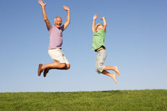 Senior man with grandson jumping in air Royalty Free Stock Photos