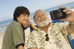 Senior Man With Grandson Taking Self-Portrait. Senior men with grandson taking self-portrait through digital camera on beach Stock Photography