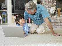 Senior man and grandson (5-7) using laptop on living room floor, smiling Stock Photography