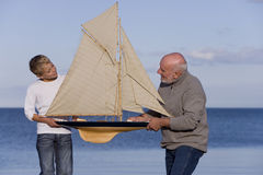 Senior man and grandson (7-9 years) holding up model sailboat by sea, smiling at each other Stock Image