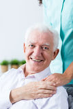 Senior man grateful for the care. Senior happy men appreciating help and care of his nurse. Holding his hand on caregiver's hand Royalty Free Stock Photos