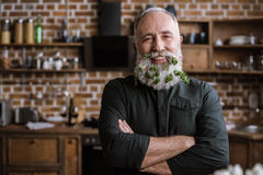 Senior man with greens in beard. Portrait of confident handsome senior man with greens in beard smiling at camera Royalty Free Stock Images