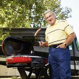 Senior man grilling. Senior adult man grilling hotdogs with RV in background Stock Image