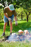 Senior man grilling chickens Stock Images
