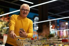 Senior Man in Grocery Store. Portrait of modern senior man grocery shopping in supermarket pulling shopping cart and smiling, copy space stock photos
