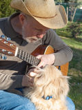Senior man with guitar petting dog Stock Photography